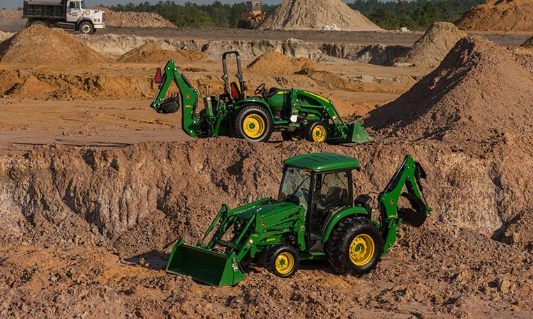 Two 4000 Series Tractors with loaders are working in dirt mounds.