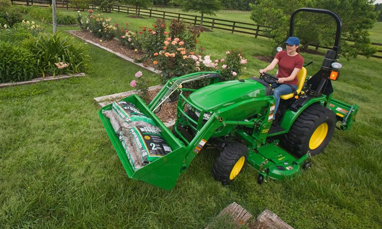 Woman driving compact tractor with loader