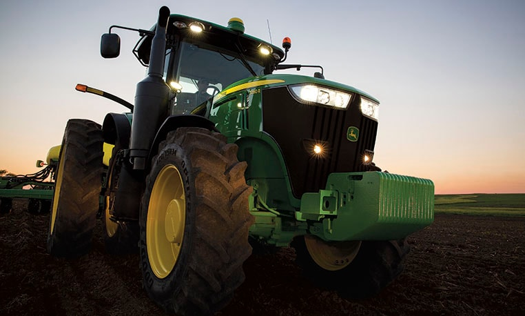 7R tractor drives through the field at night.