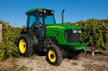 5083EN Narrow Series Tractor driving through a vineyard with blue sky in the background