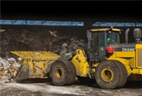 A John Deere Crawler Loader moves waste
