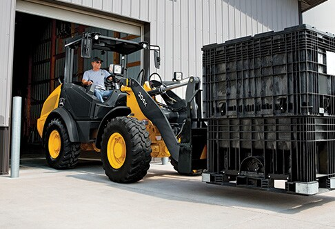 204K Compact Loader exiting from machine shed