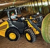 204K Compact Loader moving a round hay bale in shed