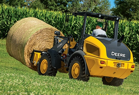 204K Compact Loader moving a round hay bale out in the field