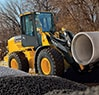 544K Wheel Loader with forks traveling with a cement stormwater pipe
