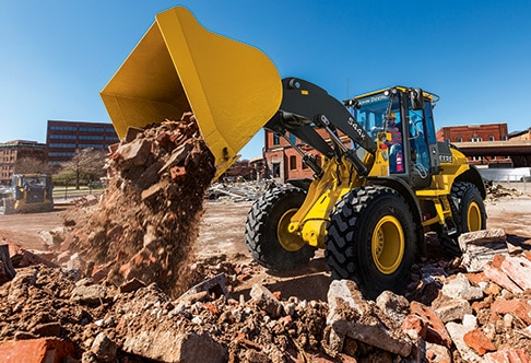 544K Wheel Loader dumping a bucket of bricks into a pile from a demolition site
