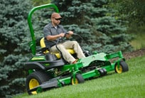 Man operating riding mower