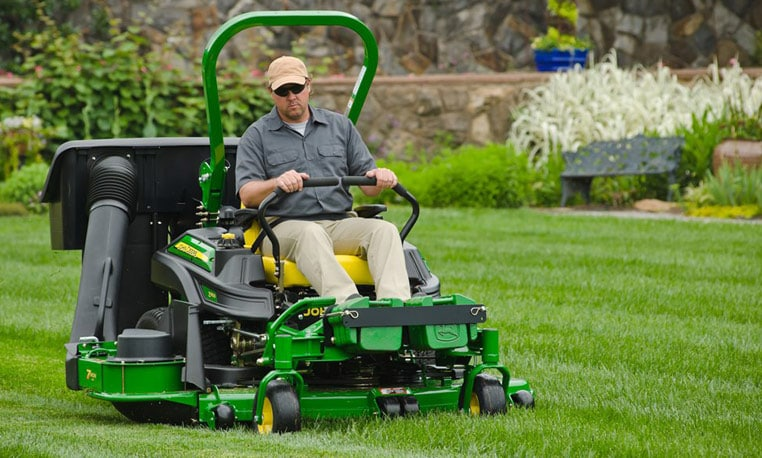 Man using a ZTrak Z900 B Series mower to trim grass at a commercial building