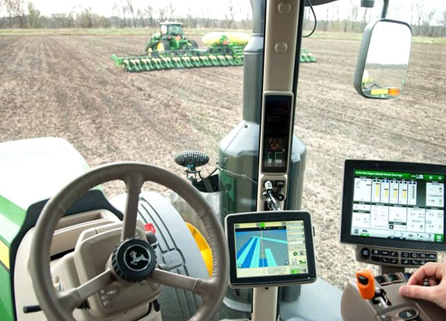 View from the inside of a John Deere tractor cab with displays and steering wheel in the foreground