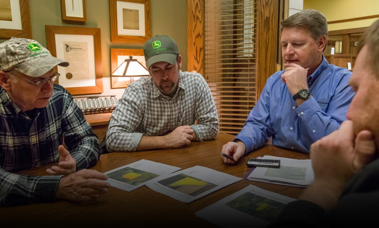 four men sitting around table reviewing precision ag in their farm operation