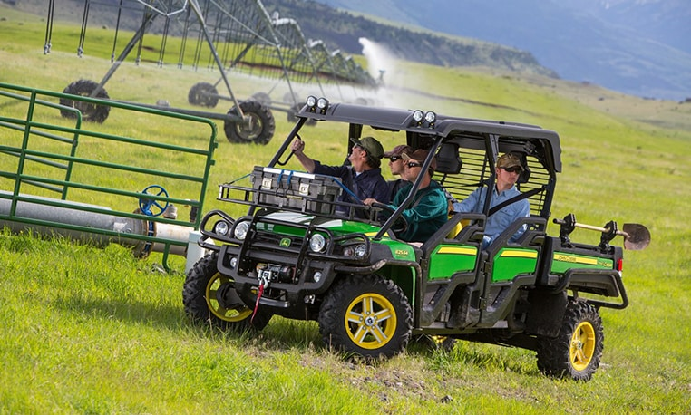 Four men in a XUV825i S4 with a toolbox and shovel checking out the irrigation in a field