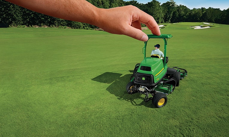 A large hand pushes an A Model Mower around a golf course as if it were a toy