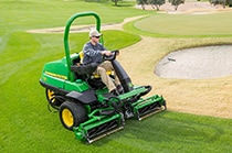 Man cuts grass on a golf course near a bunker using a PrecisionCut mower