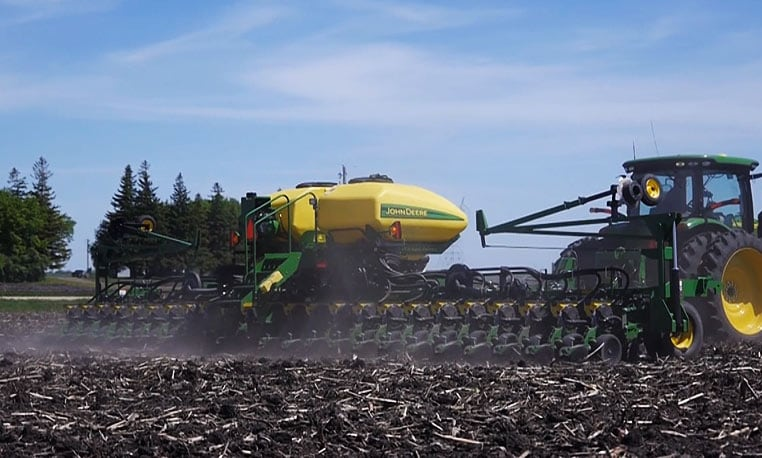 Planter moving through field linking to planting video