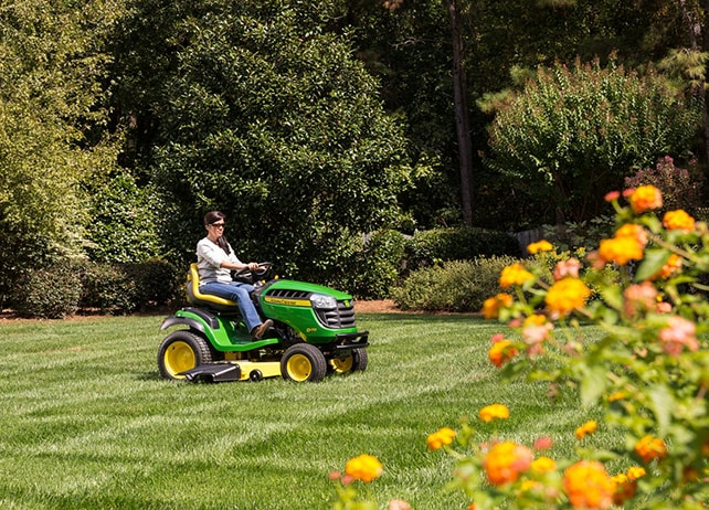 Woman driving D170 lawn tractor