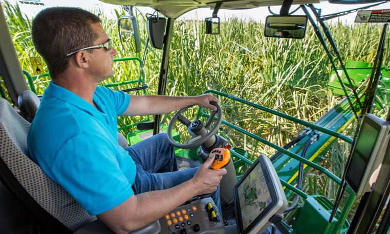 Image of man at the wheel of the cab of a harvester
