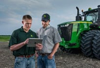John Deere dealer and farmer reviewing information on a tablet with a 9R tractor in the background