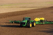 9470R Tractor with planting attachment working in a field