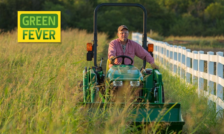 Man driving a tractor in a field.