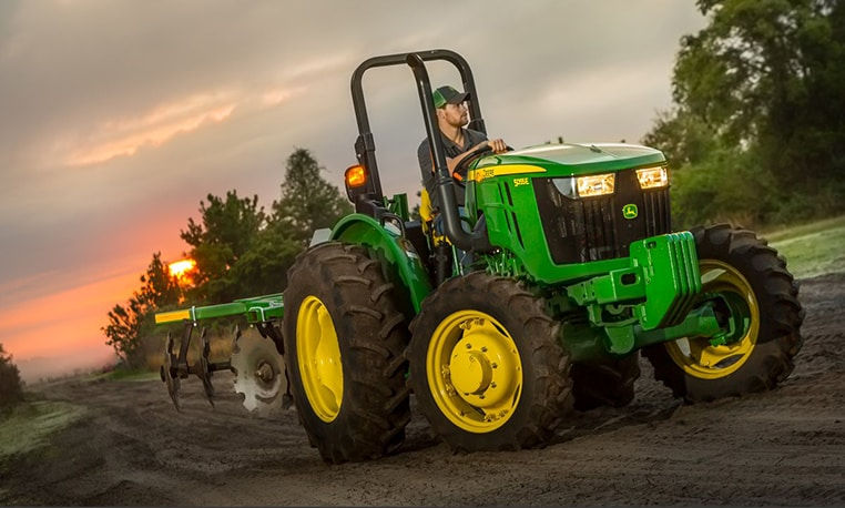 Man is driving a lit up 5E tractor with implements through a dirt path at dusk