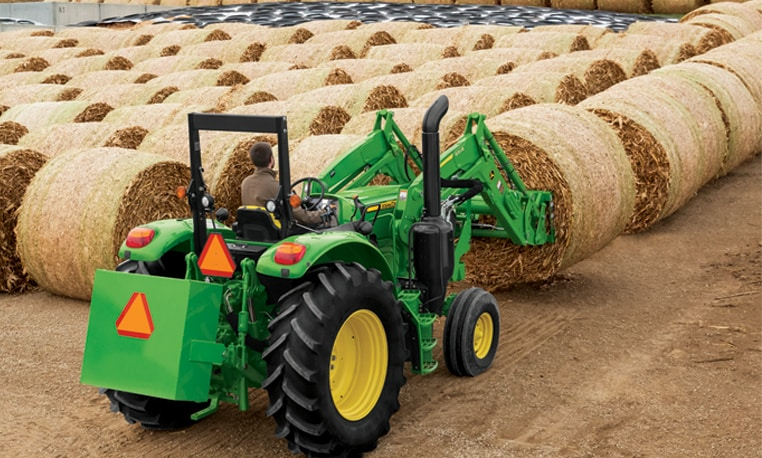 6M Series tractor with loader lifting bales