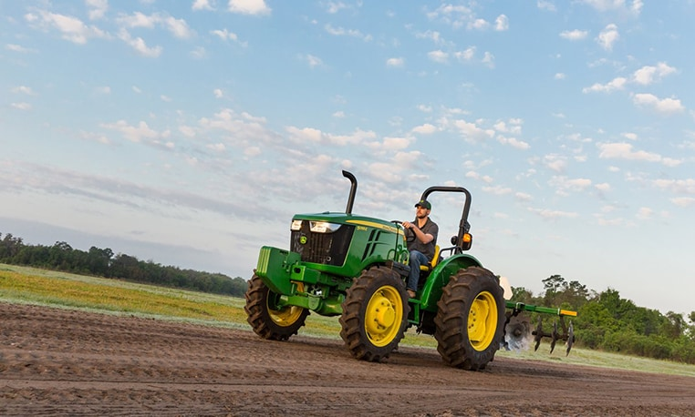 Man driving 5E tractor with Frontier implements through a field