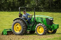 Man using a 5075M Utility Tractor with rotary tiller attachment to till soil in a field