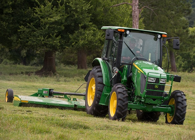 5085M Utility Tractor mowing grass