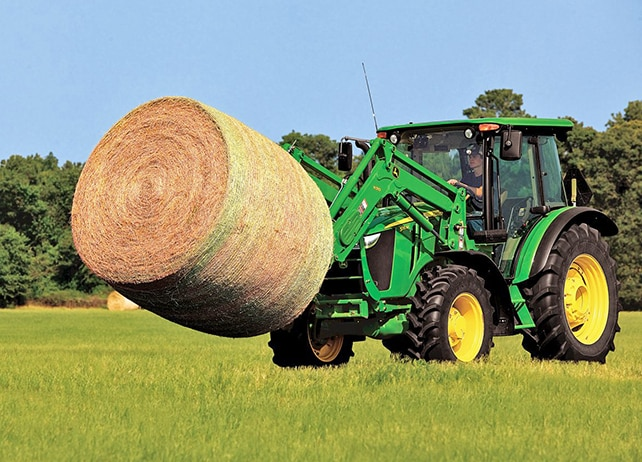 A 5115M Utility Tractor hauls a large round bale
