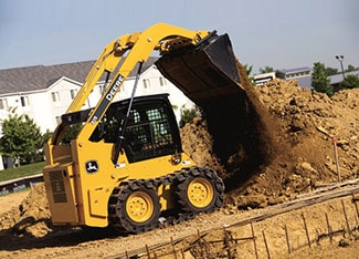Skid steer with steel tracks unloading dirt at a job site
