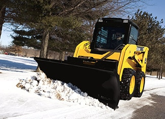 Skid Steer with snow/utility blade attachment clearing snow on a tree-lined path