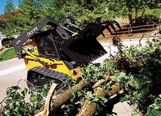 Skid Steer using a brush tined grapple attachment to lift downed tree limbs