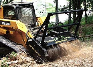 Skid Steer using mulching head attachment to mulch material in a forest