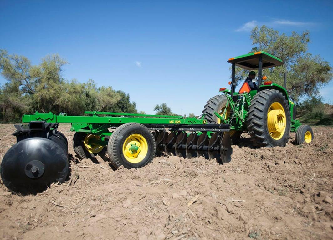 Rastra MX225 en el campo con tractor John Deere.