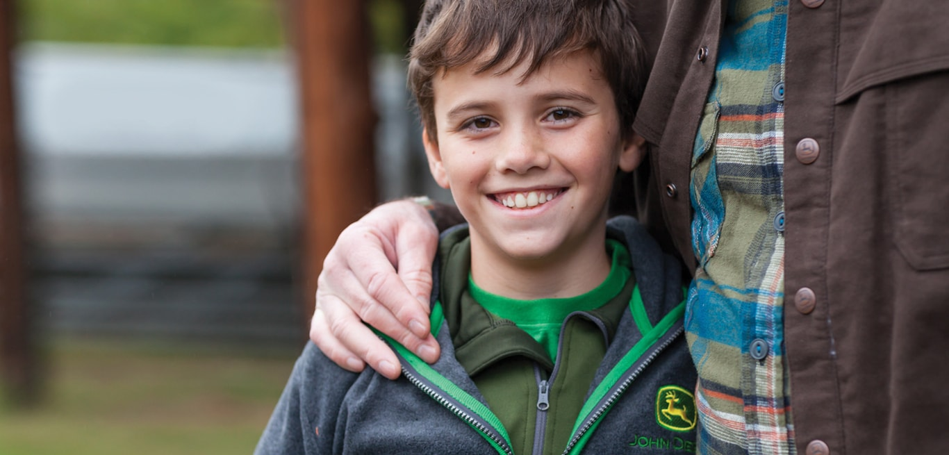 A young boy wearing a John Deere sweatshirt