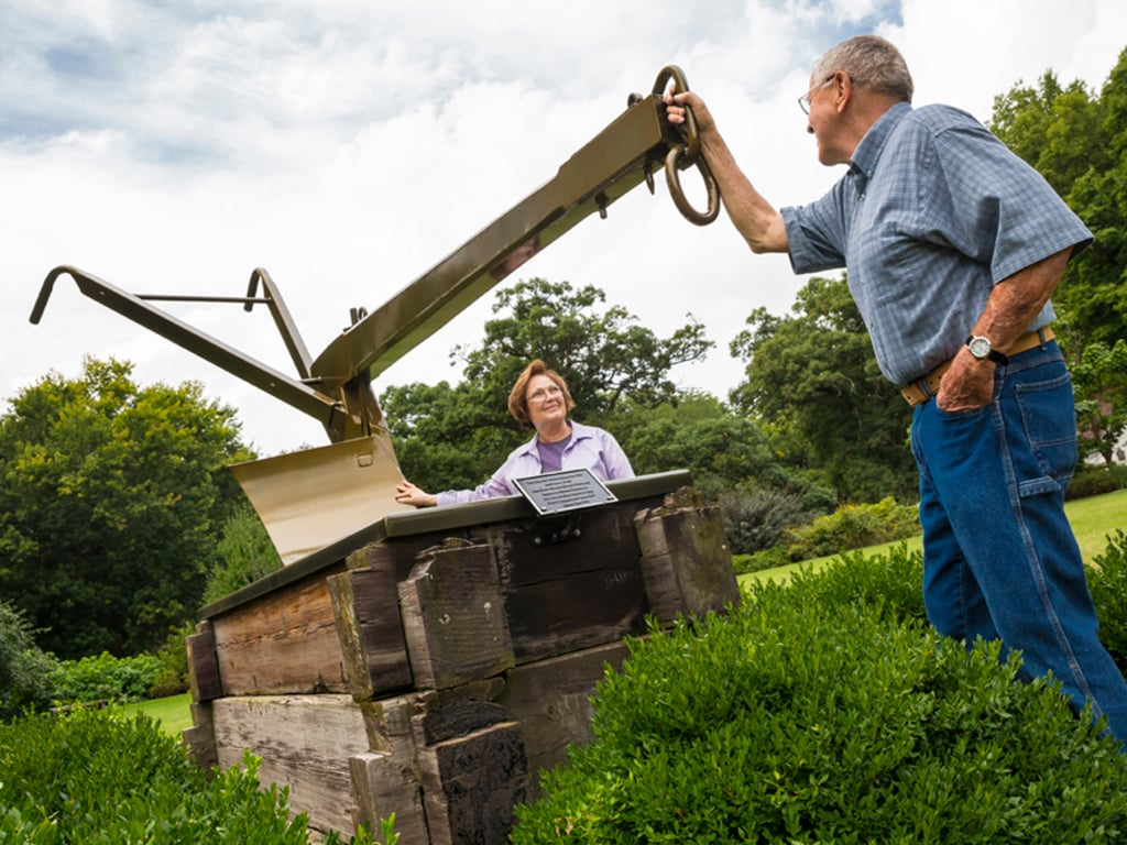 A man and woman examine a replica of John Deere's original plow