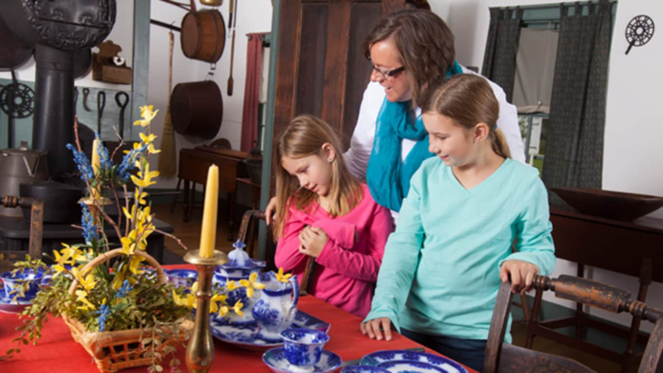 A woman and two girls look at an early table setting in the John Deere family home