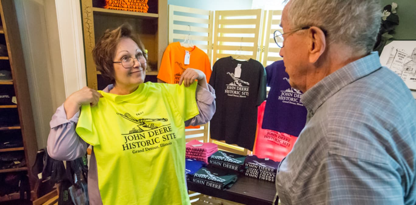 A woman holds up a John Deere Historic Site t-shirt