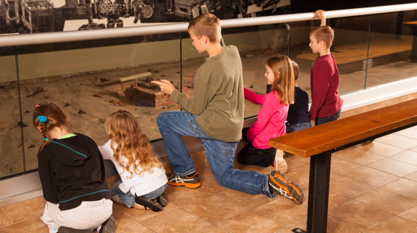 A group of children crouch down to look at an exhibit