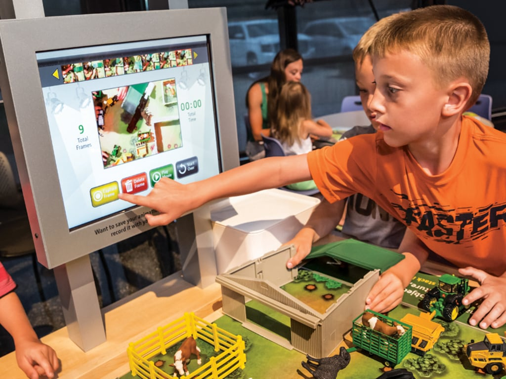 A boy touches video screen as part of an interactive farm exhibit