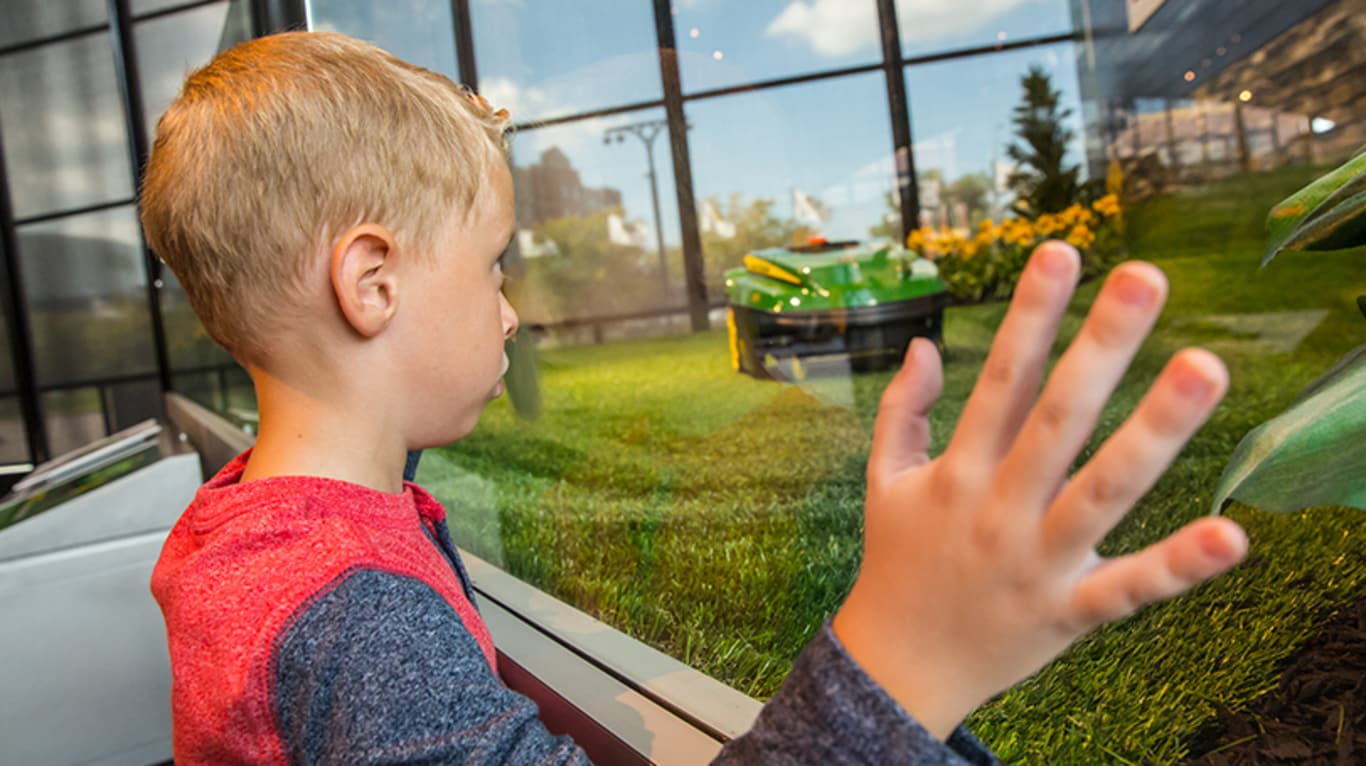A boy looks on at the autonomous mower demonstration