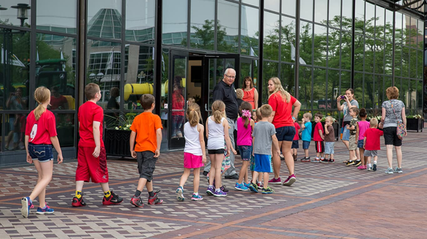 A group of kids gather outside of the John Deere Pavilion