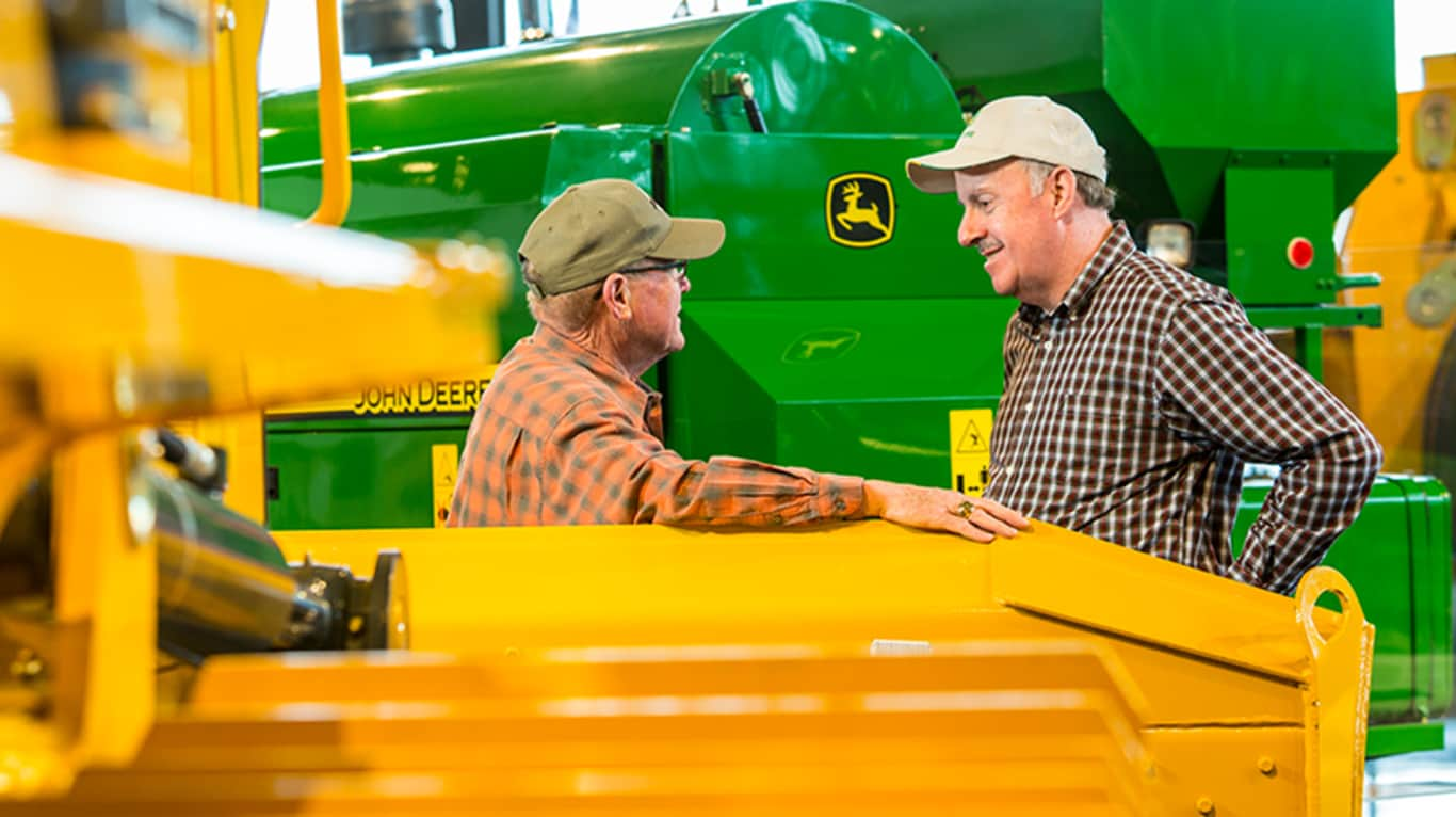 Two men have a discussion amongst John Deere machinery
