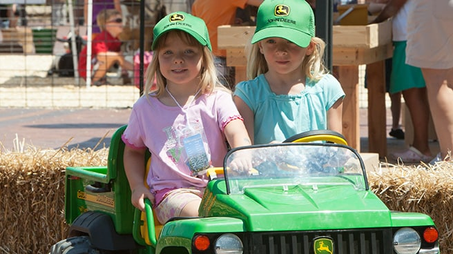 two girls on a powered ride-on gator toy