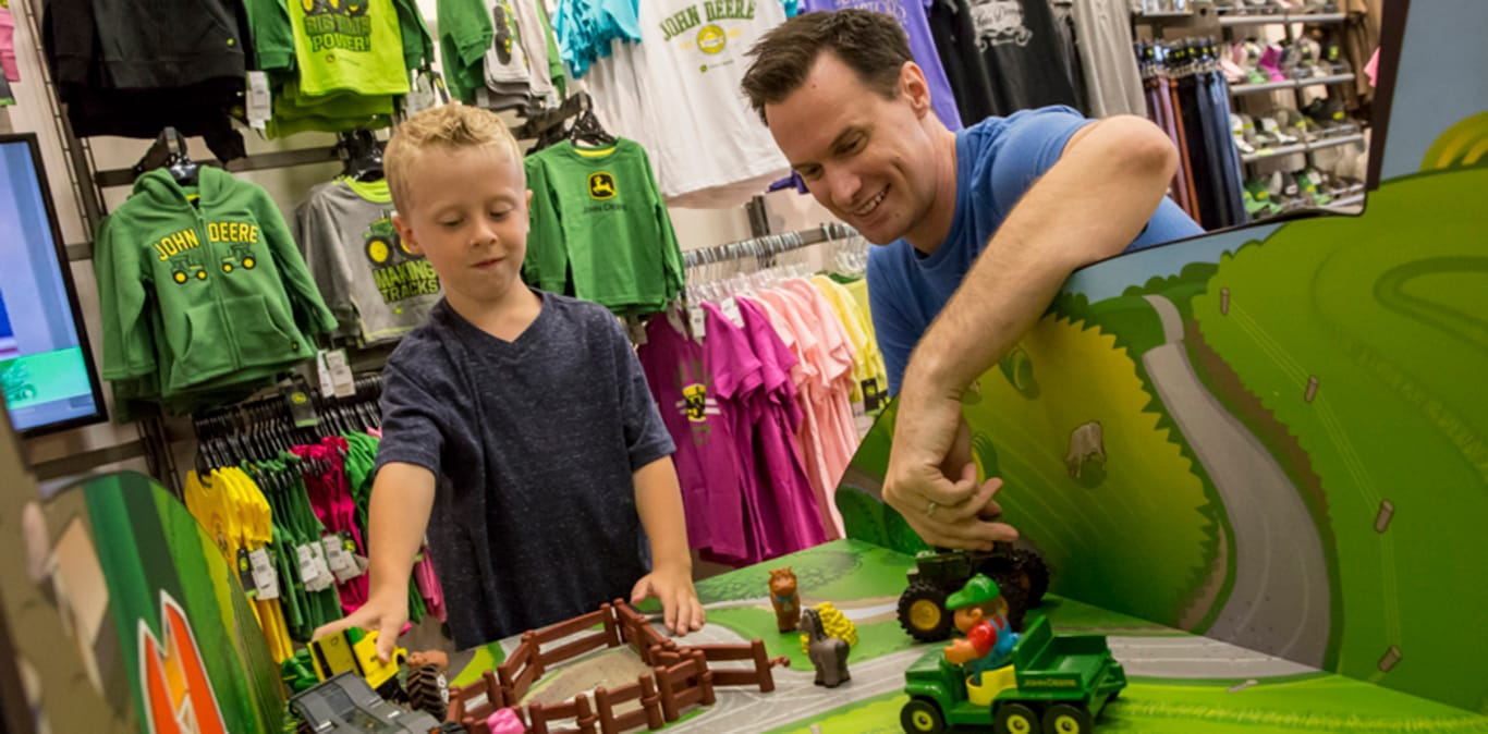 A father and son play with toy tractors in the gift shop