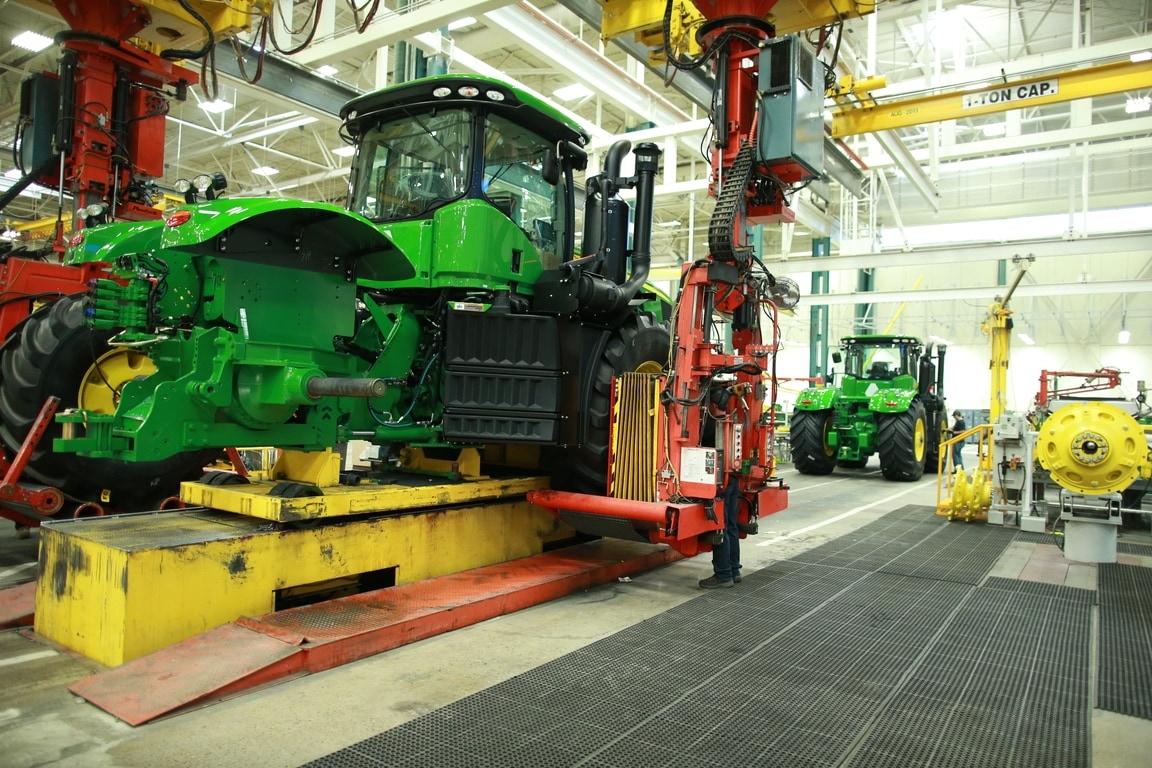 A wheel is put into place as a John Deere tractor moves down the assembly line