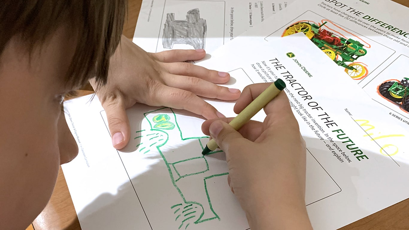 A boy drawing a tractor on an activity lesson