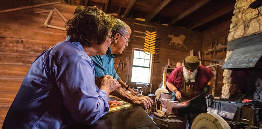 A couple looks on as a blacksmith works on a project