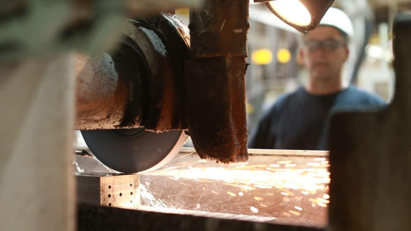 Sparks fly from a piece of metal as it is being milled