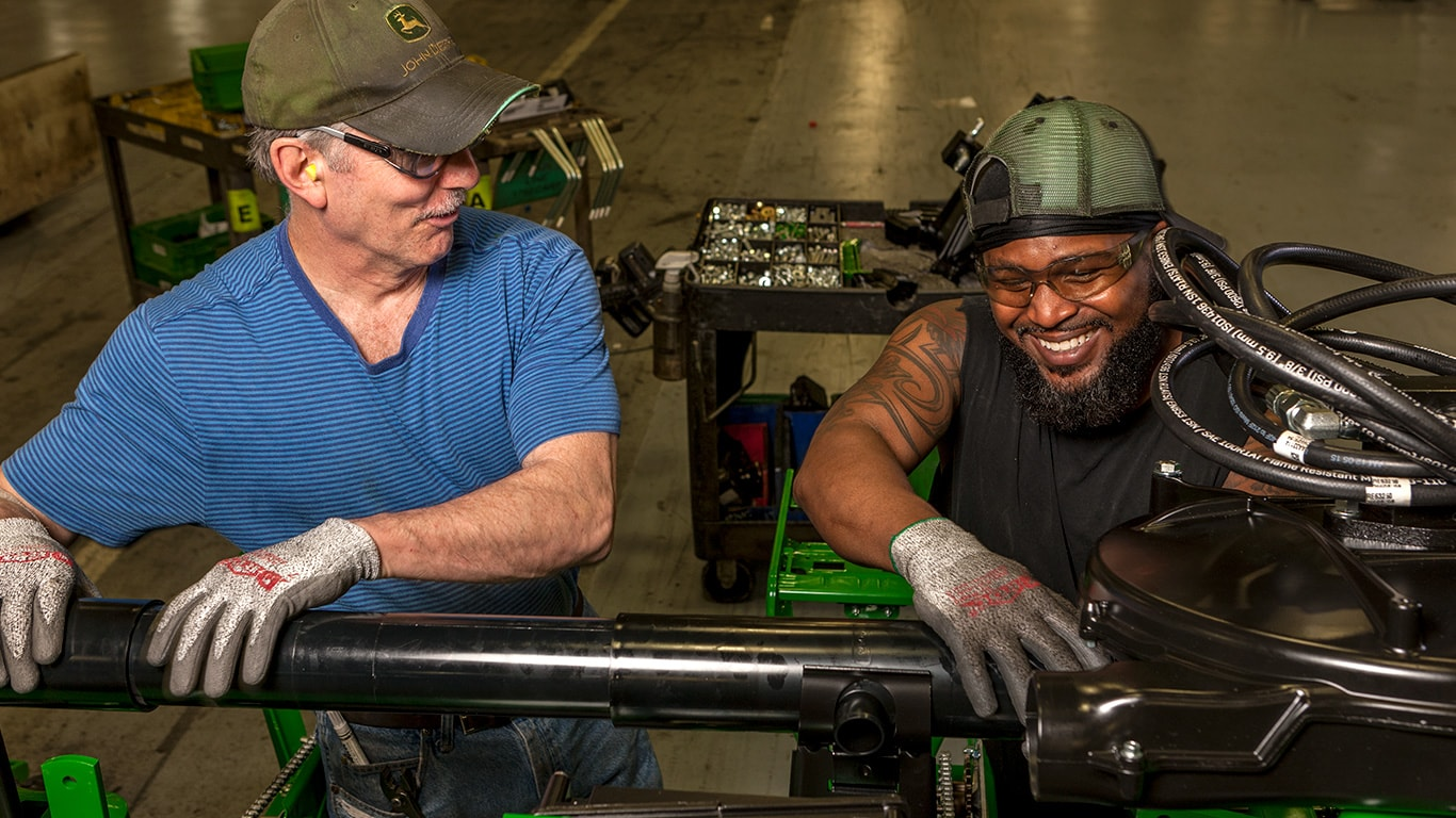 Two workers share a smile while working on the factory floor